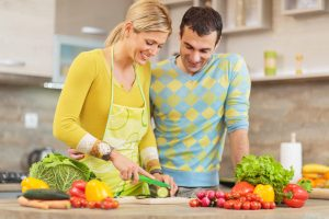 couple cutting vegetables for a healthy meal.