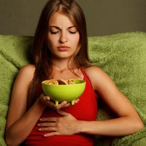 woman holding her stomach, home remedies for constipation