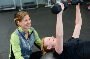 family support, woman doing dumbbell bench press