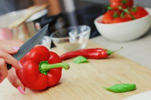 Person cutting red bell peppers. Nutrition after bariatric surgery.